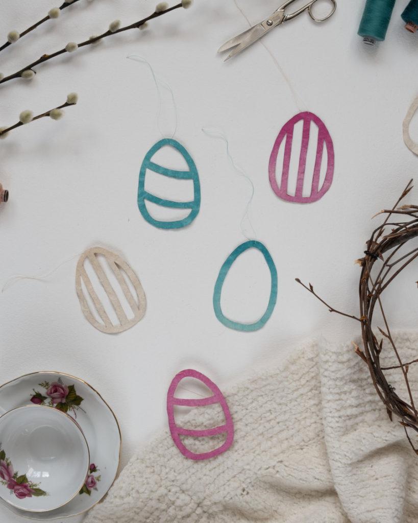 verschiedenen DIY upcycling Osterei Anhänger aus Tetrapack sind auf einer weißen Unterlage ausgebreitet