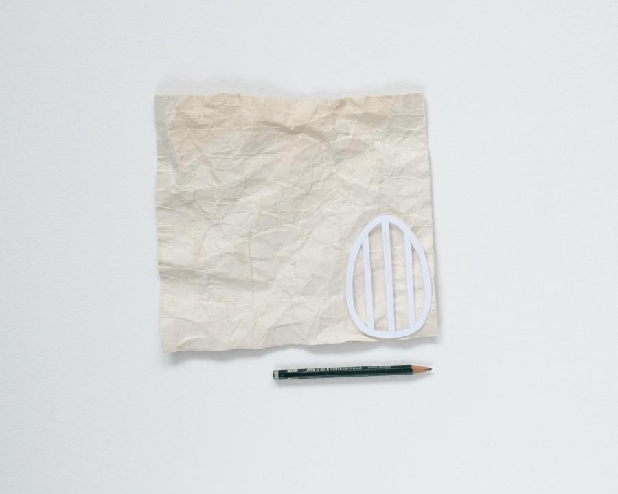 Ein Tetrapack auf dem die Osterei Vorlage liegt und ein Stift darunter um die Vorlage darauf abzuzeichnen