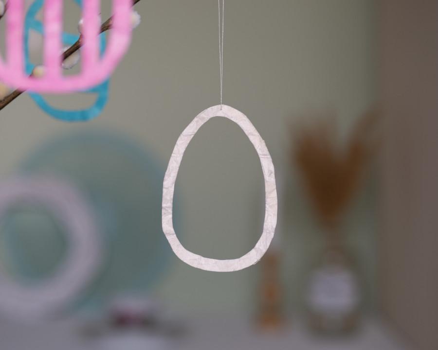 Ein Osterei ohne Farbe hängt von einem Ast runter