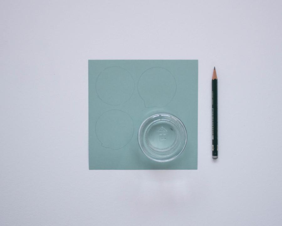 Ein Glas steht auf einem Stück Pappe und mit Hilfe der Öffnung werden die Kreise für die Zahlen aufgezeichnet