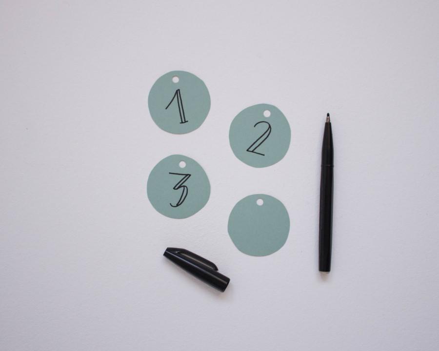 Die Zahlen von eins bis vier werden auf die Kreise für den Adventskranz aufgeschrieben