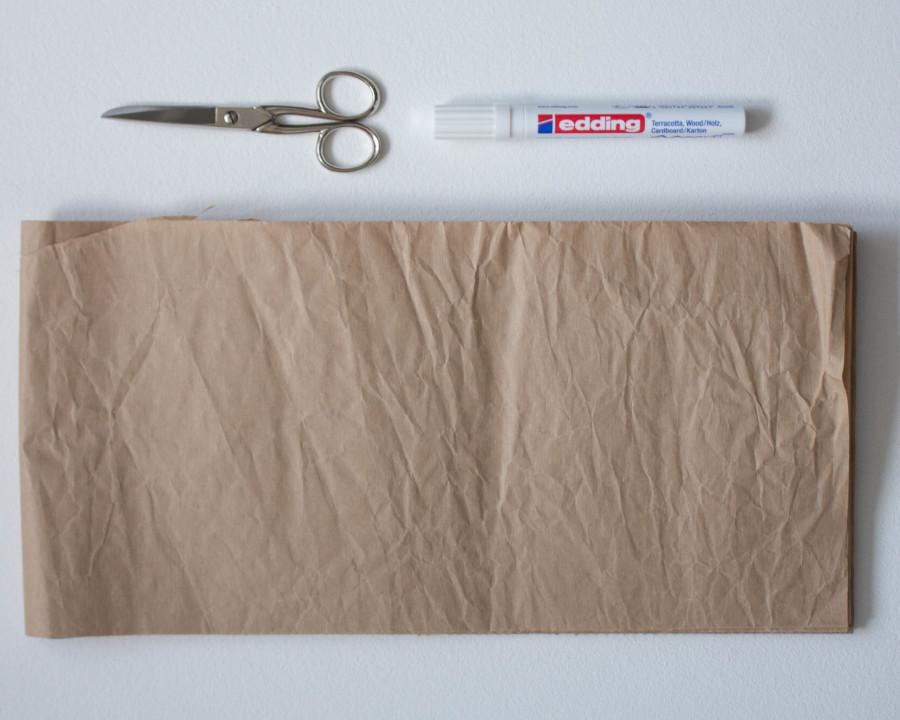 Für die DIY upcycling - weihnachtliche Verpackung brauchst du eine Schere, einen weißen Stift, Packpapier und eine Nähmaschine