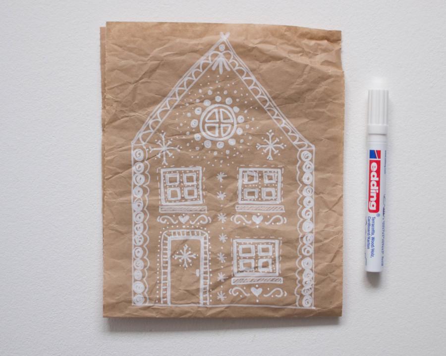 Zeichne mit dem weißen Stift ein Lebkuchenhaus auf das Packpapier